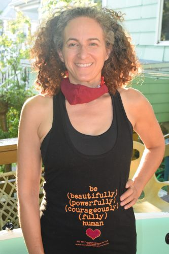 "Happy customer, Julia, wearing the ""be (beautifully) (powerfully) (courageously) (fully) human"" tank top design with the heart under the text, also sporting a warm smile, her pandemic mask off for a moment."