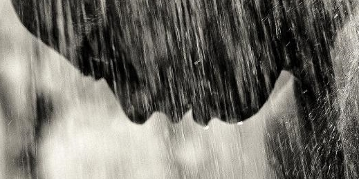 portrait from side of man hanging his head as water pours over him as if in heavy rainshower, close-up in black and white