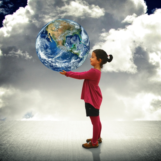 creative photo composite image of child holding the earth in her hands against, a backdrop of grey clouds