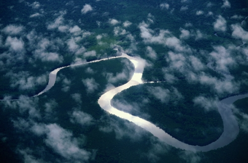 aerial view of a long winding river coursing through a lush green landscape
